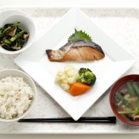 All the flavor without all the calories: This set meal from Sekai Bunka Publishing's company cafeteria includes grilled salmon with vegetables, boiled shungiku (edible chrysanthemum) and shiitake, miso soup and a bowl of half-milled rice — and it only comes to around 500 kcal. | SEKAI BUNKA PUBLISHING