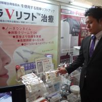 Beyond skin deep: A salesman at the 35th annual meeting of the Japan Society of Aesthetic Plastic Surgery on Oct. 11-12 showcases a Korean thread face-lift, which he says revitalizes facial skin and smoothes out wrinkles.   TOMOKO OTAKE
