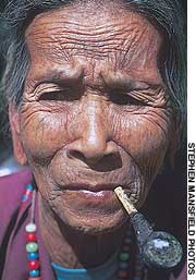 Facial tattooing is now virtually extinct among the Laotian hill tribes, but traces of an old tattoo can be seen on the face of this Lave elder (above). A Kaw woman wears a head-dress of dyed feathers, beads, pom-poms and old Chinese and French silver coins (below)