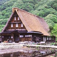 The owner of a gassho-zukuri farmhouse in Gokayama sits outside his home; the gassho-zukuri buildings have steeply pitched roofs to reduce the weight of winter snow upon them.