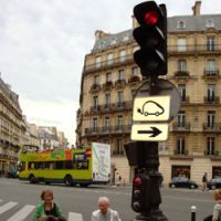 A sign on a lamppost in Paris directs drivers of electric vehicles to a recharging station.