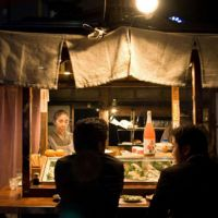 Broth brothers: Two men deep in conversation at a yatai (outdoor food stall) in the Nakasu district of Fukuoka City. | PERRIN LINDELAUF PHOTOS