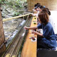 Fast food: At Hirobun diners have to snare their fresh  nagashi somen  (cold, thin wheat noodles) with chopsticks by the mouthful as they are carried along by a stream of fresh water running down a half-pipe of bamboo. Though lots of noodles escape, it's all great good fun.