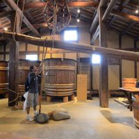 A visitor stands beneath a massive timber lever-press used to separate sake and lees. | SEAN PAVONE