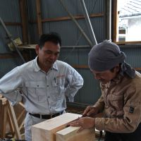 Pagoda prep (Top to bottom): Toshio Fujino, head contractor at Seirinji Temple, oversees the carving of a daitō load-bearing block; Fujino adjusts a model of Seirinji's pagoda-in-progress beside chisels and a long-handled yari kana (hewing knife); and Fujino, from the Nishizawa Koumuten engineering firm, explains the function of the pagoda's shinbashira (heart pillar). | KIT NAGAMURA PHOTOS