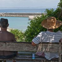 Two locals sit in the shade and gaze out over the harbor.