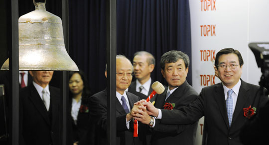 Proud moment: Calbee Inc. President Shuji Ito (right) rings the bell at the Tokyo Stock Exchange as his company's stock debuted on the first section Friday.   KYODO PHOTO