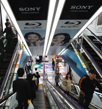 Captive audience: Shoppers pass Sony ads as they ride escalators at a store in Tokyo on Thursday. | AP PHOTO