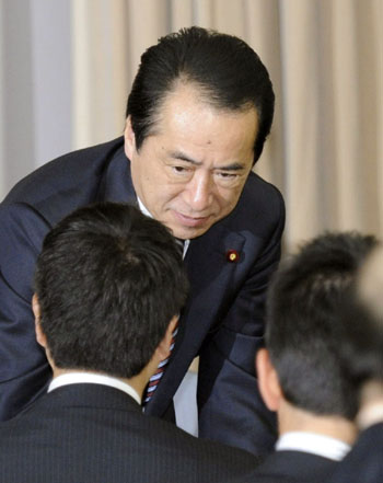 One foot out: Prime Minister Naoto Kan greets a colleague during a meeting of Democratic Party of Japan lawmakers at the Diet on Wednesday. | KYODO PHOTO
