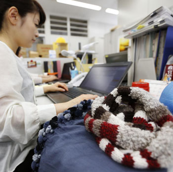 Down to business: With a scarf and lap blanket brought from home beside her, an Environment Ministry official works in her office on the first day of this year's Warm Biz campaign Thursday. | KYODO