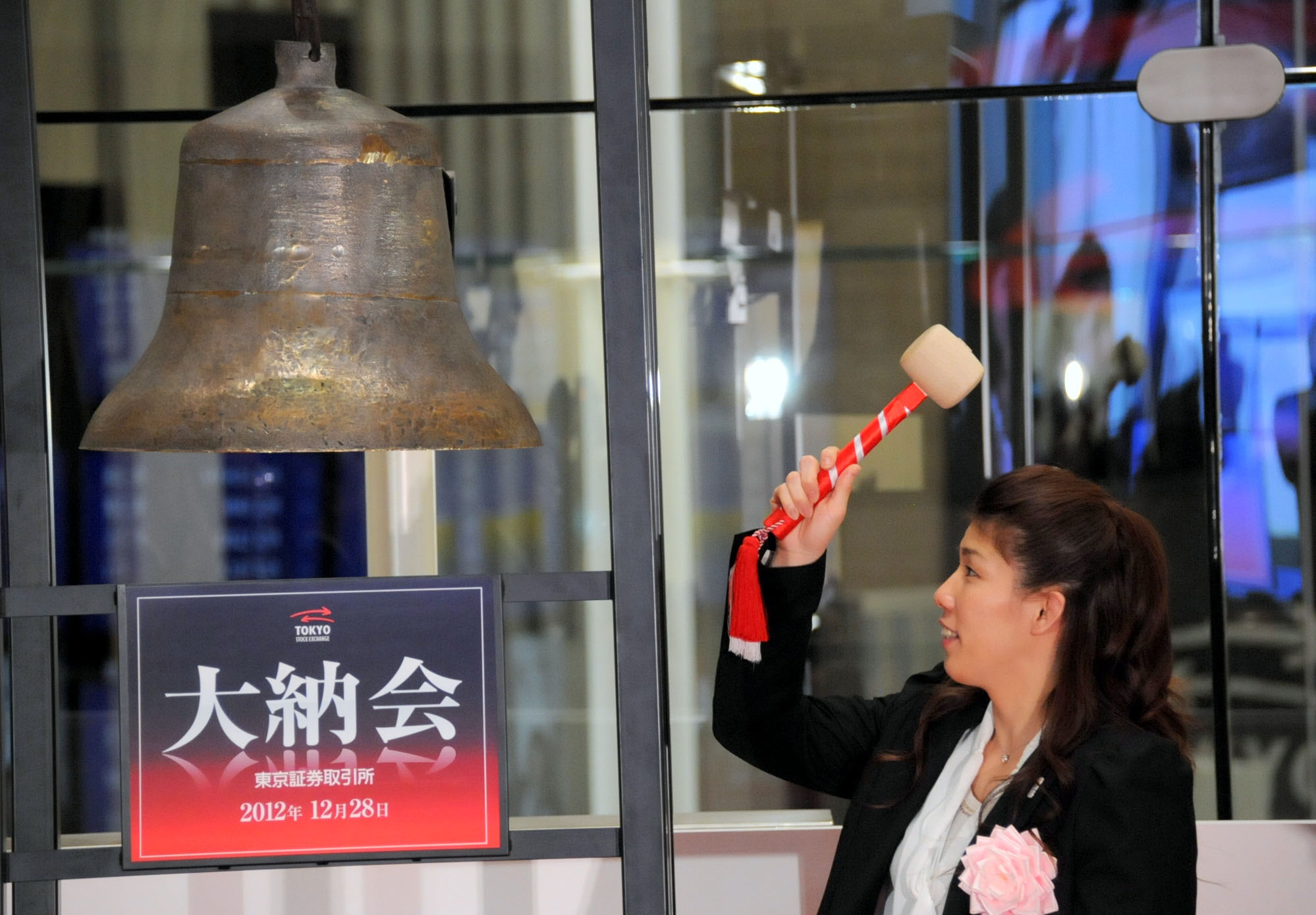 Final takedown: Wrestler Saori Yoshida, who won three consecutive Olympic gold medals in the Women's Freestyle 55 kg weight category, rings the bell Friday to mark the end of 2012 trading on the Tokyo Stock Exchange. | SATOKO KAWASAKI