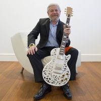 Heir guitar: Abe Reichental, president and chief executive officer of 3D Systems Corp., poses for a photograph last April in San Francisco with a Les Paul guitar that was made using a 3-D printer. | BLOOMBERG