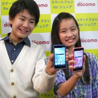 Coming to a classroom near you: Teen models show off NTT DoCoMo's new smartphone targeting youths around junior high school age in Tokyo's Otemachi district Thursday. | KAZUAKI NAGATA