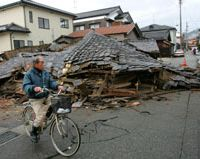 A man bicycles past a flattened house a day after the March 25 earthquake. | AP PHOTO