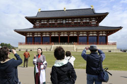 Glorious past: Visitors take photos in front of the rebuilt Daigoku-den Hall after it was reopened to the public to commemorate the 1,300th anniversary of the ancient capital Heijo-kyo in Nara on April 24. | KYODO PHOTO