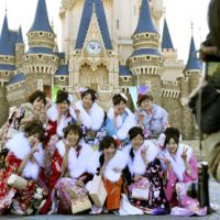 Real life: People celebrating turning 20 this year pose in front of Cinderella Castle during the Coming-of-Age ceremony Monday at Tokyo Disneyland in Urayasu, Chiba Prefecture. | KYODO PHOTO