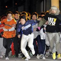 Good luck: Runners bolt from the starting line Monday at Nishinomiya Shrine in Nishinomiya, Hyogo Prefecture, to race for the title of 'Lucky Men' of the year. | KYODO PHOTOS