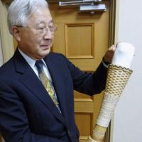 A step ahead: Toshiro Nakamura, founder and president of Nakamura Brace Co., holds an artificial leg made with bamboo and other local materials by Philippine artisans at his company in Omori, Shimane Prefecture. | KYODO PHOTO