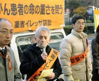 Seeking to settle: Akio Chikazawa (second from left), one of the plaintiffs suing the government and AstraZeneca K.K., the Japanese subsidiary of British drugmaker AstraZeneca, over side effects caused by the lung cancer drug Iressa, speaks Tuesday outside the health ministry. | KYODO PHOTO