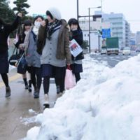 Snow avoiding it: High-school students head for their test venues in Yonago, Tottori Prefecture, on Saturday. Two days of grueling university entrance exams kicked off the same day. | KYODO PHOTO
