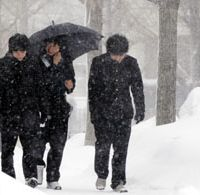 Determined: High-school students make their way through heavy snow in the city of Tottori for their second round of entrance examinations Sunday. The exams were delayed by up to an hour due to snow at 20 testing venues in Hokkaido and seven other prefectures, including Tottori. | KYODO PHOTO