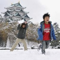 Good packing: A father and son play in the snow Monday in Nagoya Castle park in Kita Ward. | KYODO PHOTO
