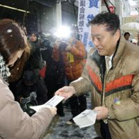 Picking sides: Nagoya Mayor Takashi Kawamura hands a flier to a local voter that endorses the Feb. 6 referendum on whether to dissolve the city assembly. | KYODO PHOTO