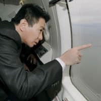 Look but don't touch: Foreign Minister Seiji Maehara views the disputed island of Kunashiri off Hokkaido aboard a Japan Coast Guard plane in December.   KYODO PHOTO