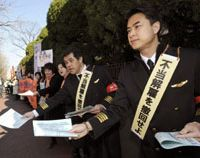 Suited up: Dismissed Japan Airlines captains and cabin attendants hand out leaflets Wednesday outside the Tokyo District Court after filing suit against the former flagship carrier now under corporate rehabilitation. | KYODO PHOTO