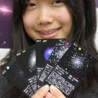 Star search: A student holds up some of the astronomy game cards created by college students and space fans in Tokushima Prefecture. | KYODO PHOTO