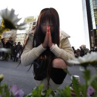 A woman prays at the site of the 2008 stabbing spree in Tokyo's Akihabara district on Sunday. The district partially reopened the weekly 'pedestrian paradise' zone later in the afternoon after closing it off for more than two years after the fatal attack. | AP PHOTO