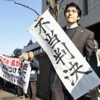 It's not over: A lawyer holds a sign that reads 'unjust decision' Friday after the Tokyo High Court ruled the metropolitan government was not in the wrong for ordering his clients — teachers and other high school staff — from observing the national anthem and flag in school ceremonies.   KYODO PHOTO