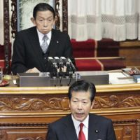 Center stage: New Komeito chief Natsuo Yamaguchi (front) delivers a speech during an Upper House plenary session Friday as Takeo Nishioka, the chamber's president, looks on. | KYODO PHOTO
