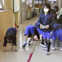 Extracurricular: Children clean a hallway covered with volcanic ash at their elementary school Monday in Takaharu, Miyazaki Prefecture. | KYODO PHOTO