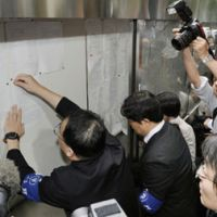 It's official: An official from the Tokyo District Court posts a notice detailing the decision to indict Democratic Party of Japan 'shadow shogun' Ichiro Ozawa outside the court house in Chiyoda Ward on Monday. | KYODO PHOTO
