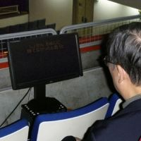 Inclusive: Subtitles appear on a display for a man with a hearing disability at a Tokyo theater in November.   KYODO PHOTO