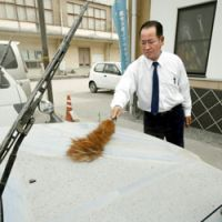 Fallout: A cabby in Takahara, Miyazaki Prefecture, wipes ash from the hood of his car after a nearby volcano erupted for the sixth and seventh times in a week Wednesday.   KYODO PHOTO