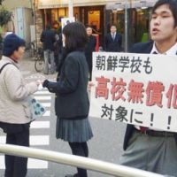 Petition drive: Students from a pro-Pyongyang school seek signatures in front of JR Jujo Station in Kita Ward, Tokyo, last March for a petition seeking the inclusion of pro-Pyongyang schools in the government's high school tuition waiver program. | KYODO PHOTO