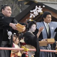 Wrestling with their demons: Yokozuna Hakuho (left), stablemaster Takanohana (center) and Bulgarian ozeki Kotooshu take part Saturday in a setsubun bean-throwing event intended to dispel demons in Uji, Kyoto Prefecture. | KYODO PHOTO