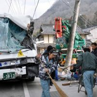 School adventure: A wrecked school bus sits on a road in Niimi, Okayama Prefecture, Monday morning after a truck-mounted crane clipped it while changing lanes, forcing it to crash.   KYODO PHOTO