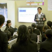 The spiel: A worker from eyeglass company JIN Co. explains the company's operations to foreign students at a job recruiting event in Osaka on Jan. 15. | KYODO PHOTO