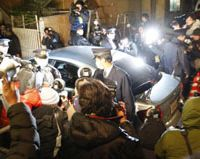 On the scent: Photographers flock to a car carrying murder suspect Yoshiaki Kimura as it arrives at Meguro Police Station in Tokyo early Friday.   KYODO PHOTO