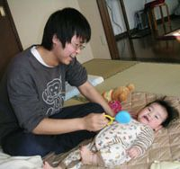 Mr. Mom: Masashi Nihei, a 30-year-old stay-at-home husband in Kanagawa Prefecture, entertains his baby son at their home in January. | KYODO PHOTO