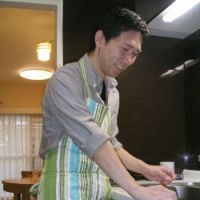 Takatoshi Miyauchi, 31, also a stay-at-home dad, prepares a meal last month while looking after his younger daughter in Tokyo. | KYODO PHOTO