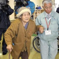While the getting is good: An elderly woman is escorted to a shelter Thursday in Miyakonojo, Miyazaki Prefecture, after evacuating her home near Mount Shinmoe amid the threat of rain-triggered volcanic ash slides.   KYODO PHOTO