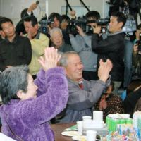 Referendum verdict: Supporters of former Akune Mayor Shinichi Takehara applaud the dissolution of the municipal assembly in a referendum in Kagoshima Prefecture on Sunday. | KYODO PHOTO