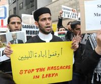 In solidarity: Protesters shout slogans against Libyan leader Moammar Gadhafi in front of the Libyan Embassy in Tokyo's Daikanyama district Wednesday. | SATOKO KAWASAKI PHOTO