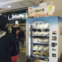 Go bananas: A girl takes a picture of a vending machine selling bunches of bananas Monday at the Tenjin downtown area of the city of Fukuoka. | KYODO PHOTO