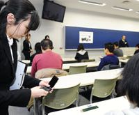 Zero tolerance: An examiner ensures a test-taker's cell phone is turned off Wednesday during the entrance exam at Taisho University in Tokyo. | KYODO PHOTO
