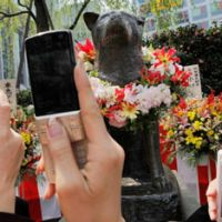 Legendary: People take photos of the Hachiko statue at Shibuya Station in Tokyo in 2009.   AP PHOTO